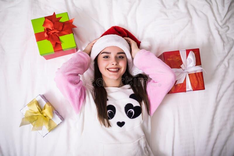 Piękno młoda kobieta w jej łóżku w bożych narodzeniach i Santa kapeluszu z prezenta widokiem od wierzchołka w domu jest ubranym obrazy royalty free