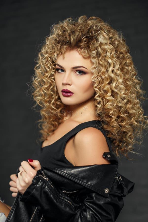 Piękno portret seksowna fryzująca włosiana blondynki dziewczyna w czarnej skórzanej kurtce Studio z ciemnym tłem obraz royalty free