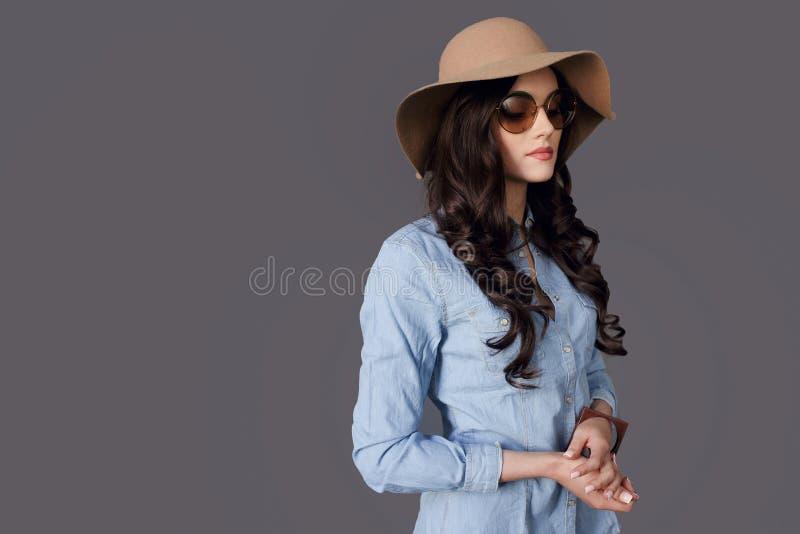 Piękno portreta brunetki młoda kobieta pozuje w profilu, wearings w kapeluszu i round okularach przeciwsłonecznych na popielatym  zdjęcia stock