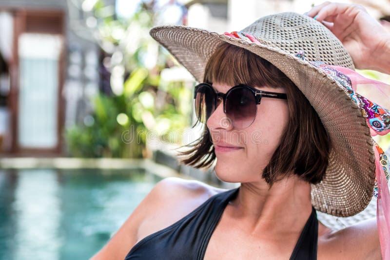Piękno seksowna kobieta z kapeluszem i okularami przeciwsłonecznymi cieszy się jej wakacje przy pływackim basenem na luksusowej w zdjęcia stock