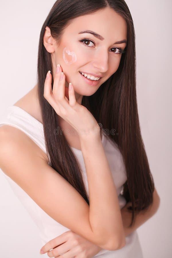 Piękno, skóry opieka i ludzie pojęć, - uśmiechnięta młoda kobieta stosuje śmietankę twarz i patrzeje odzwierciedlać w domu łazien fotografia stock