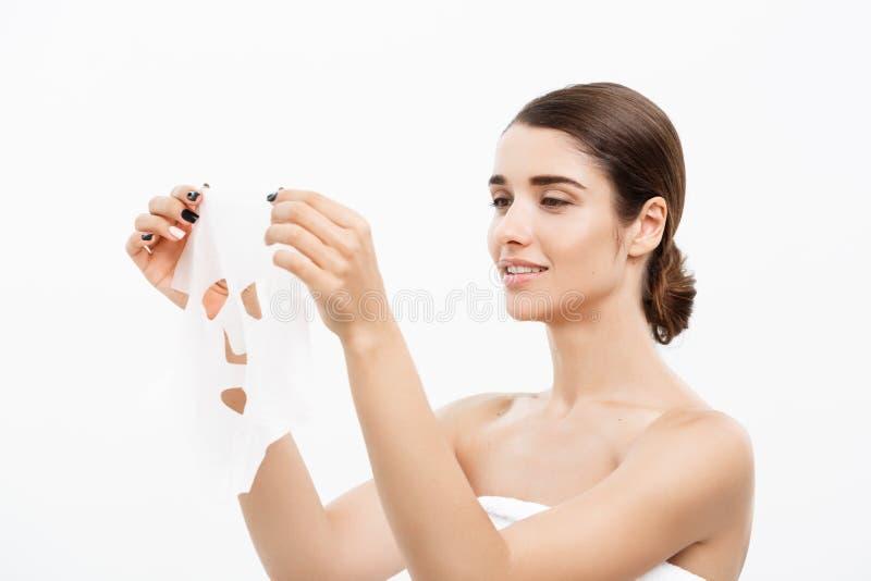 Piękno skóry opieki pojęcie - Piękna Kaukaska kobieta stosuje papieru prześcieradła maskę na jej twarz bielu tle zdjęcia royalty free