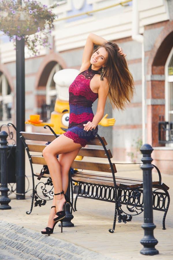 Piękno splendoru młoda kobieta w wygodnym mieście opierał jej łokcie na ławce długie włosy Modna dama z pięknym uczesaniem, mak obrazy royalty free