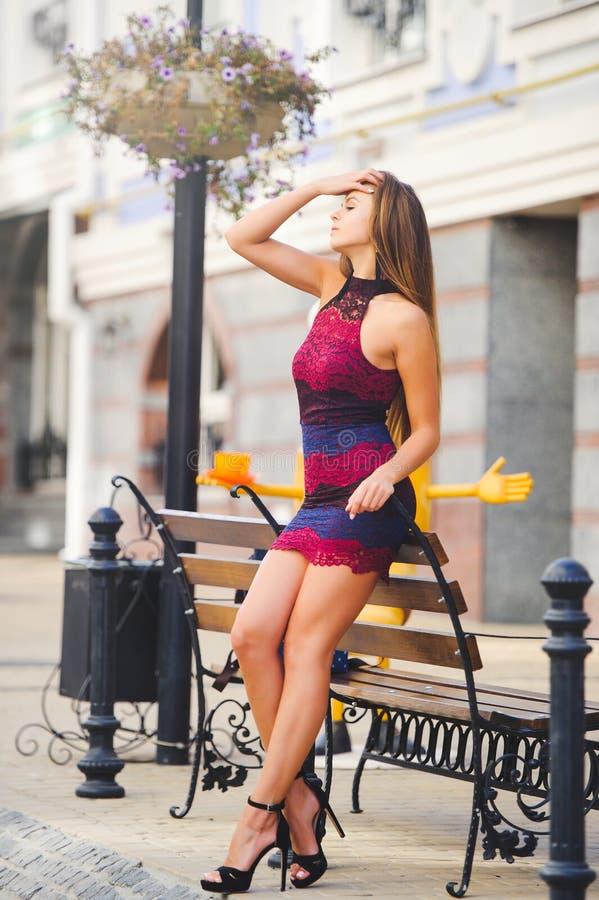 Piękno splendoru młoda kobieta w wygodnym mieście opierał jej łokcie na ławce długie włosy Modna dama z pięknym uczesaniem, mak obraz stock