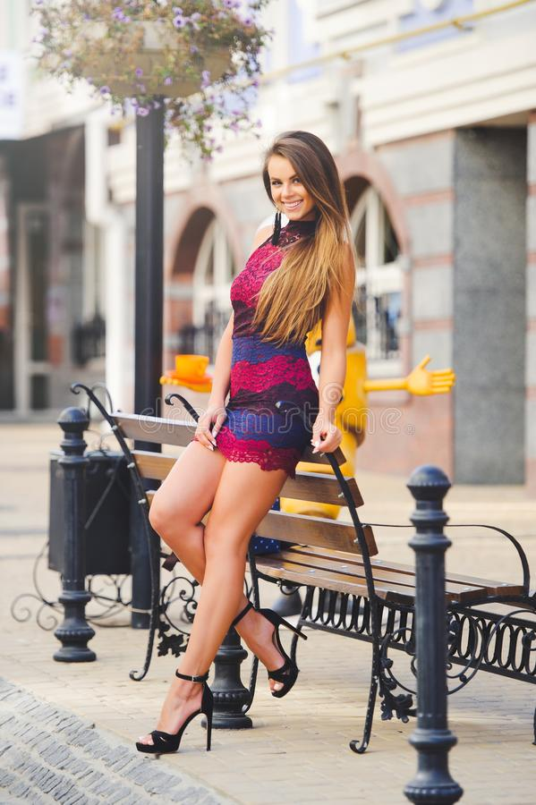 Piękno splendoru młoda kobieta w wygodnym mieście opierał jej łokcie na ławce długie włosy Modna dama z pięknym uczesaniem, mak zdjęcia royalty free