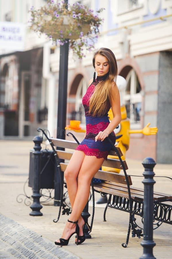 Piękno splendoru młoda kobieta w wygodnym mieście opierał jej łokcie na ławce długie włosy Modna dama z pięknym uczesaniem, mak obraz royalty free