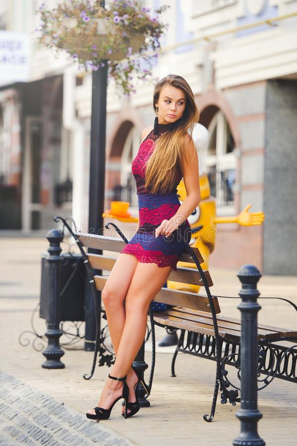 Piękno splendoru młoda kobieta w wygodnym mieście opierał jej łokcie na ławce długie włosy Modna dama z pięknym uczesaniem, mak obrazy stock