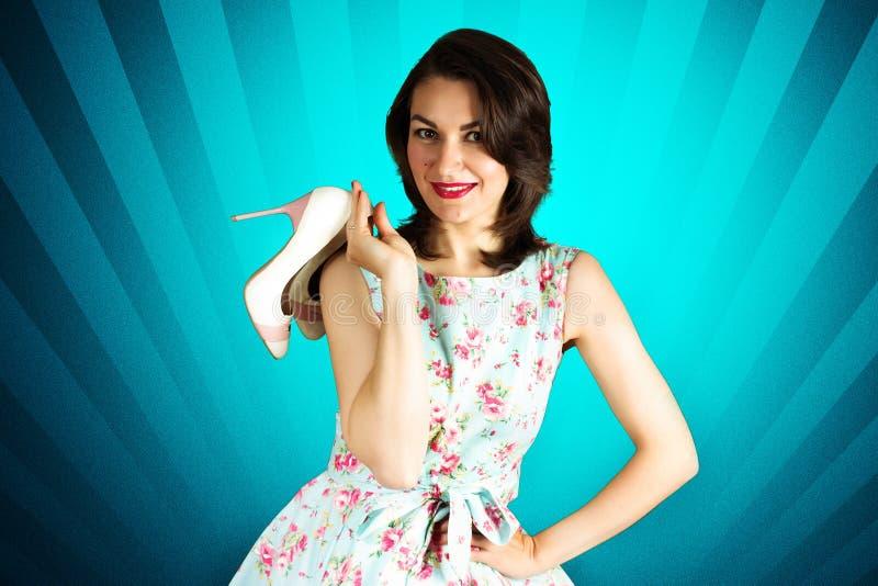 Piękno szpilki uśmiechnięta dziewczyna z butami na błękitnym tle zdjęcia stock