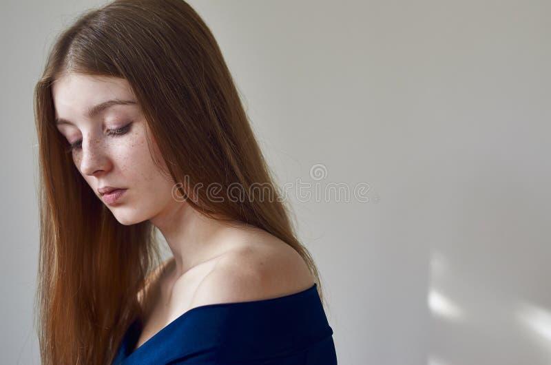 Piękno temat: portret piękna młoda dziewczyna z piegami na ona twarz i być ubranym błękitną suknię na białym tle w studi zdjęcia royalty free