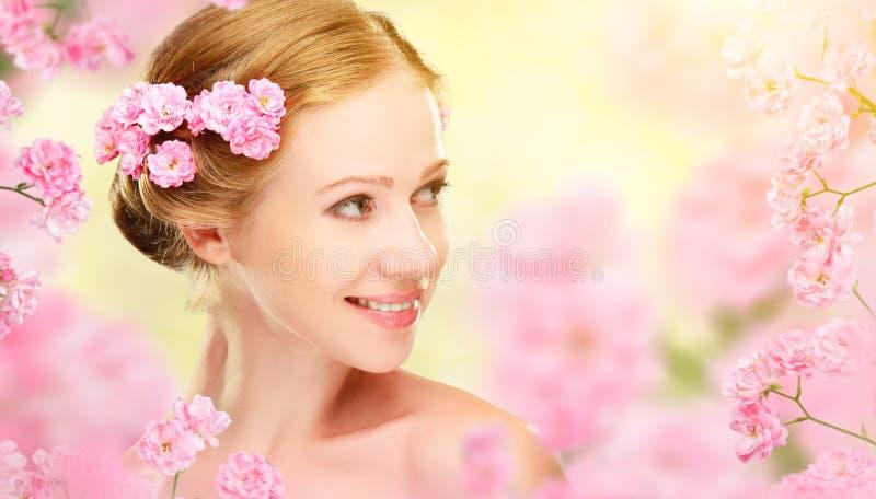 Piękno twarz młoda piękna kobieta z menchiami kwitnie w jej brzęczeniach zdjęcie stock