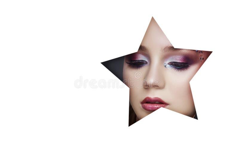 Piękno twarzy makeup młoda dziewczyna w białej księgi dziurze Kobieta z pięknym makeup, jaskrawi oczy, świecący cień w gwiazdowej fotografia stock