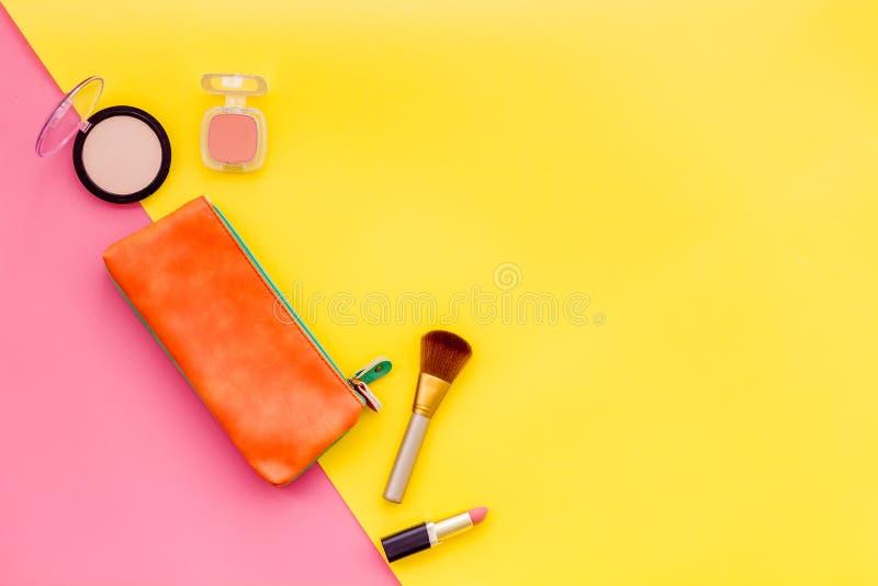 Piękno ustawiający z dekoracyjnymi kosmetykami Gwoździa połysk, muśnięcia i torba na, kolorze żółtym i menchii tła odgórnego wido obrazy stock