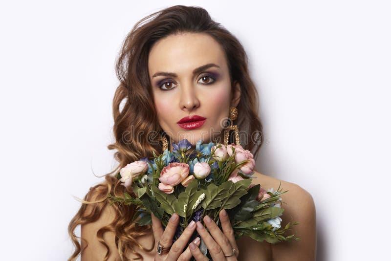 Piękno Wzorcowa dziewczyna z bukietem kwiaty Piękna młoda kobieta doskonalić brunetka wakacyjnego modnego makijażu czerwone uwodz zdjęcia royalty free