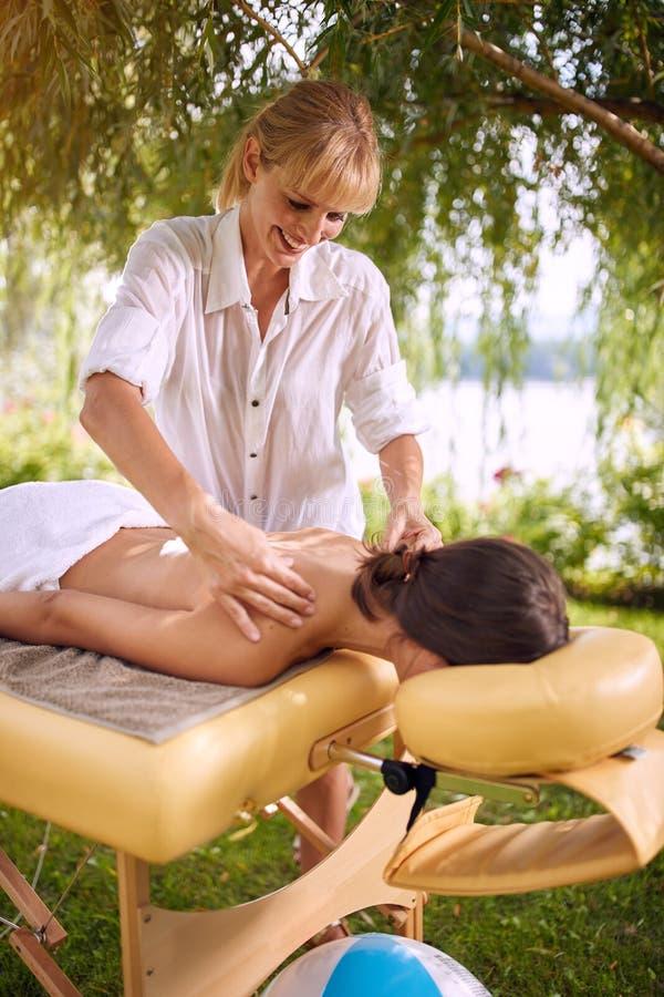 Piękno zdroju uśmiechnięty masażysta masuje kobiety w nat obrazy stock