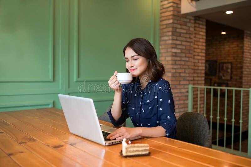 Piękny śliczny azjatykci młody bizneswoman w cukiernianym, używać lapt obraz stock