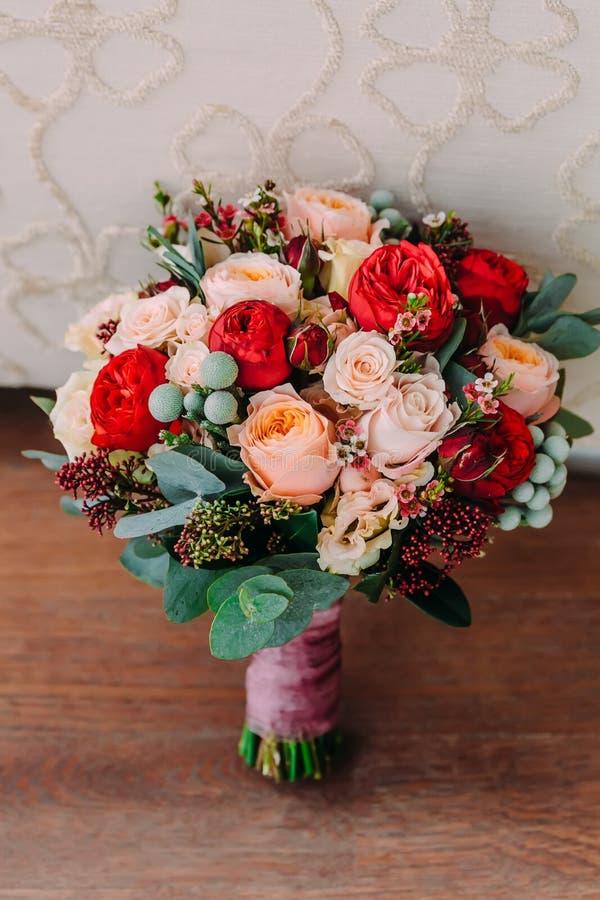 Piękny ślubny bukiet czerwień kwiaty, menchie kwitnie i greenery jest na drewnianej podłoga obraz stock