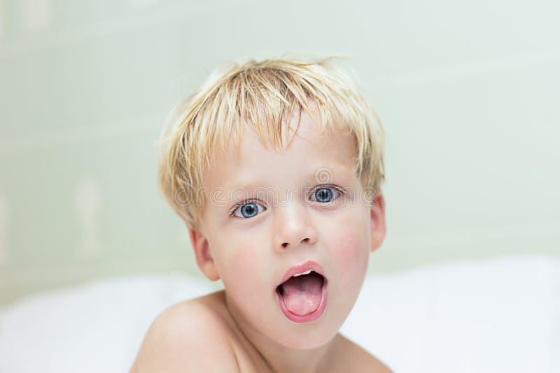 Piękny śmieszny uśmiechnięty śliczny dziecko patrzeje kamerę obraz royalty free