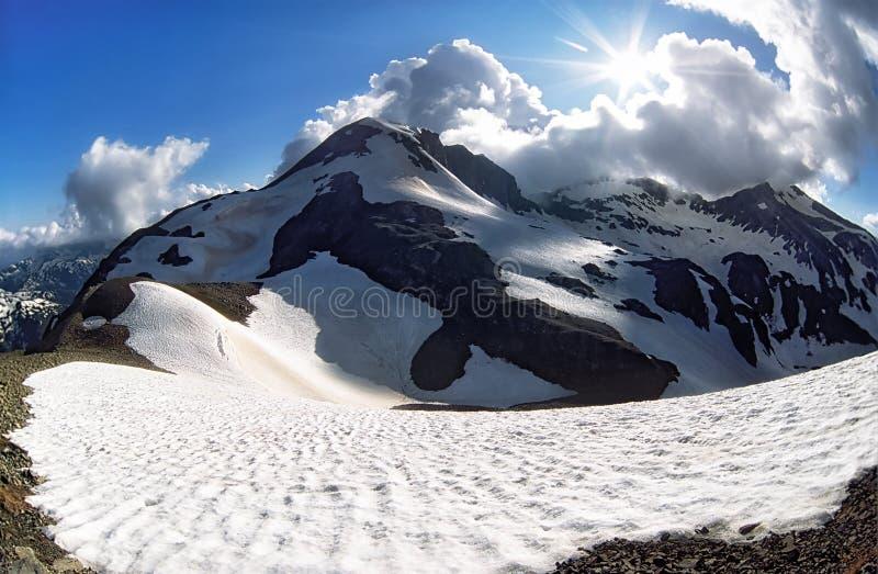 Piękny śnieżny halny szczyt i niebieskie niebo z chmurami Sceniczny zima krajobraz Główna Kaukaz grań przy zmierzchem Loyub przep zdjęcia royalty free