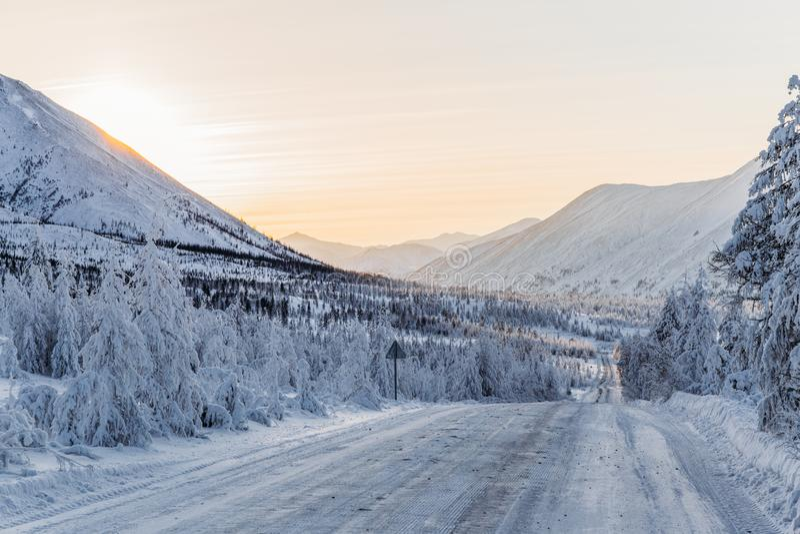 piękny śnieg zakrywał zimy drogę z drogowym znakiem i drzewa w górach, obrazy stock