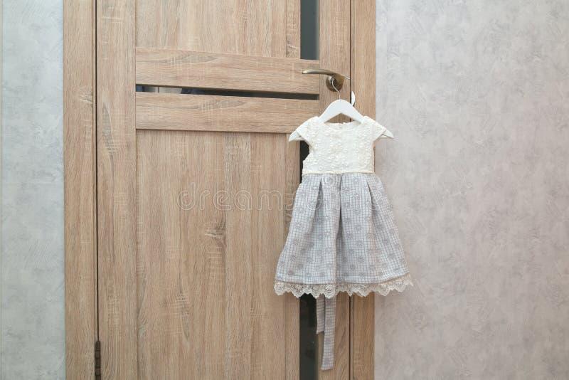 Piękny świąteczny dziecko sukni obwieszenie na drzwiowej rękojeści blisko popielatej ścianie wakacyjny narządzanie Czekać na urod fotografia royalty free