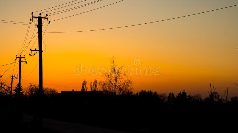 Piękny żółty lato zmierzchu zmierzch przeciw tło wiosce, budynkowi, drzewom i elektryczność liniom energetycznym, zdjęcia stock