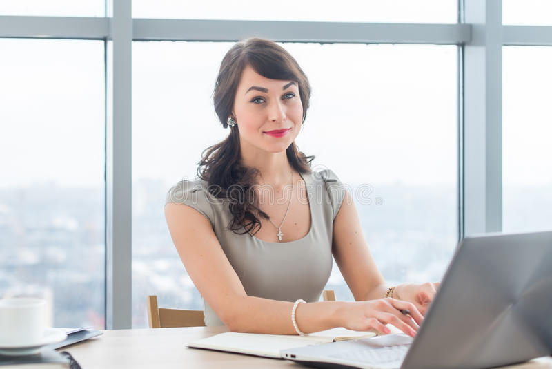 Piękny żeński copywriter obsiadanie w biurze, pisać na maszynie nowy artykuł, pracujący z tekstem, używać laptop przy miejscem pr zdjęcia stock