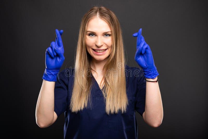 Piękny żeński dentysta jest ubranym pętaczki pokazuje palce krzyżujących obraz stock