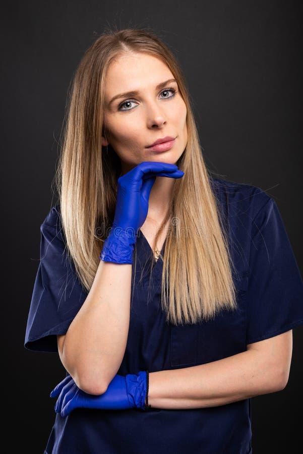 Piękny żeński dentysta jest ubranym pętaczki pozuje z ręką na podbródku obrazy stock