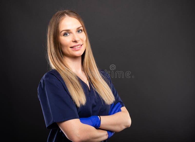 Piękny żeński dentysta jest ubranym pętaczki pozuje z rękami krzyżować zdjęcia royalty free