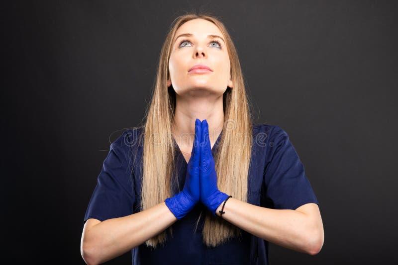 Piękny żeński dentysta jest ubranym pętaczki robi modlitewnemu gestowi obrazy royalty free