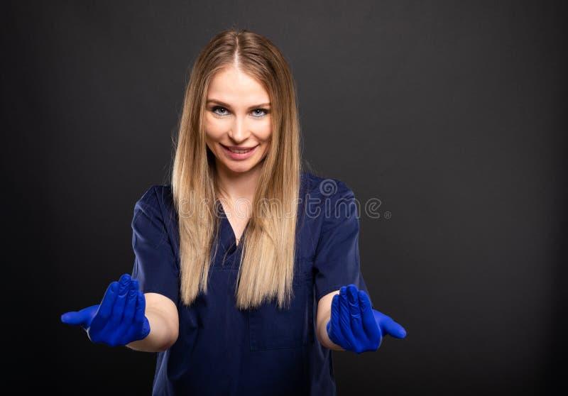 Piękny żeński dentysta jest ubranym pętaczki robi przychodzącemu tutaj gestowi zdjęcie royalty free