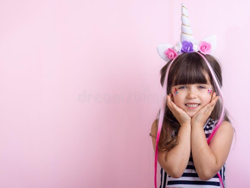 Piękny żeński dzieciak w włosianym obręczu z jednorożec modą i rogiem odziewa zdjęcia stock