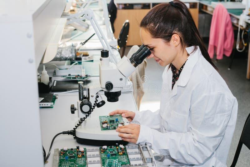 Piękny żeński komputerowego eksperta fachowy technik egzamininuje deskowego komputer w laboratorium w fabryce zdjęcie stock