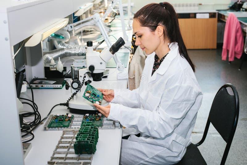 Piękny żeński komputerowego eksperta fachowy technik egzamininuje deskowego komputer w laboratorium w fabryce obraz stock