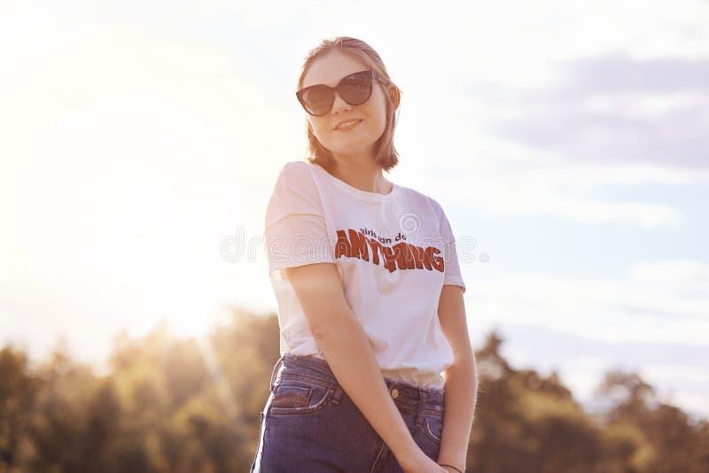 Piękny żeński nastolatek w przypadkowym stroju, jest ubranym modnych okulary przeciwsłonecznych, spojrzenia w odległość z rozważn zdjęcia stock