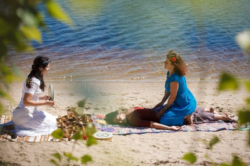 Piękny żeński odbiorczy energia dźwięka masaż z śpiewu ciała i pucharów masażem na brzeg rzeki obraz stock