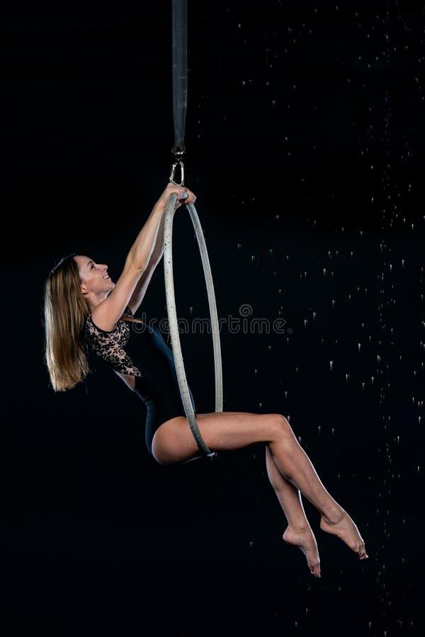 Piękny żeński powietrzny akrobata obsiadanie na powietrznym obręczu Odizolowywający na czarny tle obrazy stock