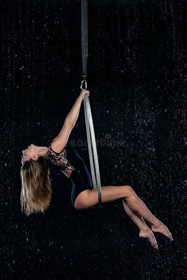 Piękny żeński powietrzny akrobata obsiadanie na powietrznym obręczu Odizolowywający na czarny tle obraz royalty free