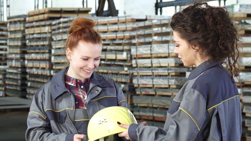 Piękny żeński pracownik fabryczny otrzymywa hardhat od jej kolegi fotografia stock