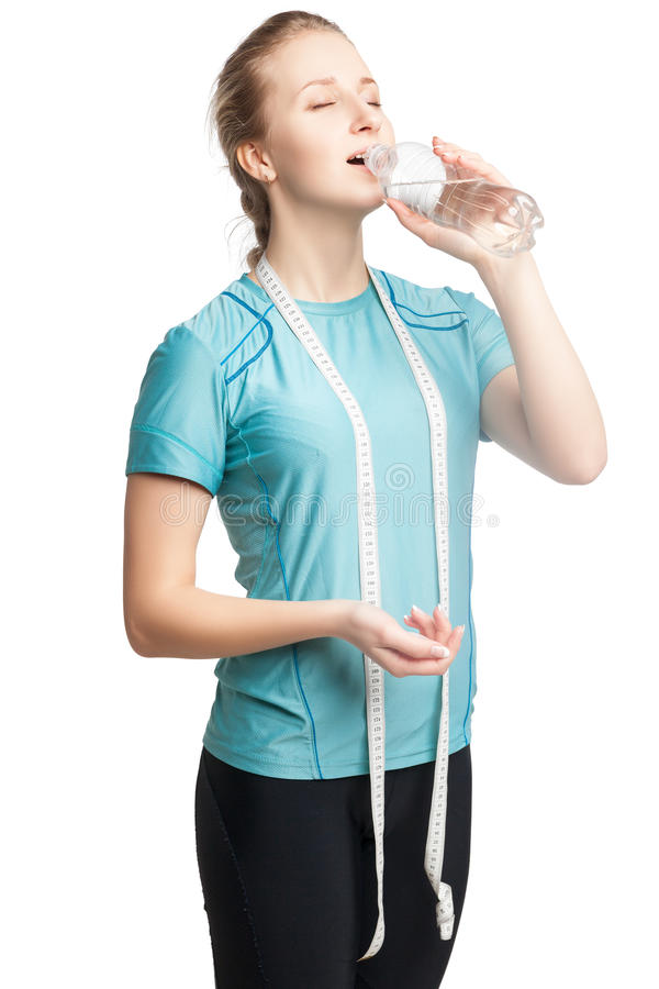 Piękny żeński sprawność fizyczna model trzyma butelkę woda, jest ubranym taśmy miarę fotografia stock