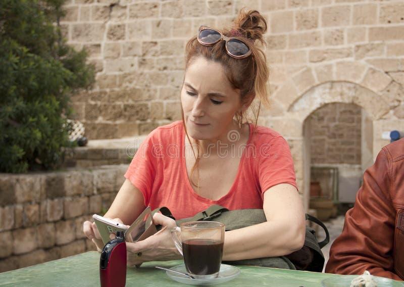 Piękny żeński turystyczny obsiadanie w plenerowej kawiarni zdjęcie stock