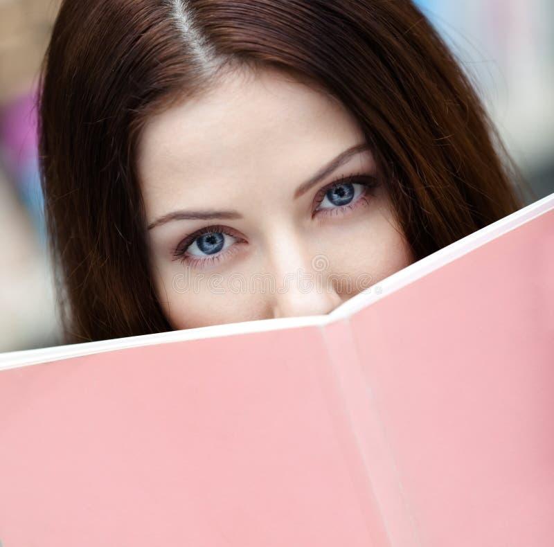 Piękny żeński uczeń czyta książkę obrazy stock