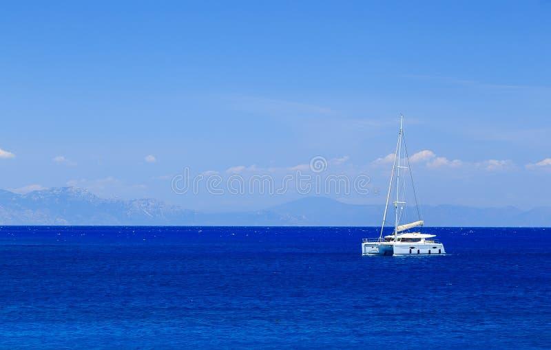 Piękny żeglowanie jacht przy morzem na tle odległe wyspy Grecja obrazy royalty free