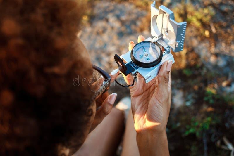 Piękny afrykański dziewczyny obsiadanie na skale w jarze, patrzeje kompas obraz stock