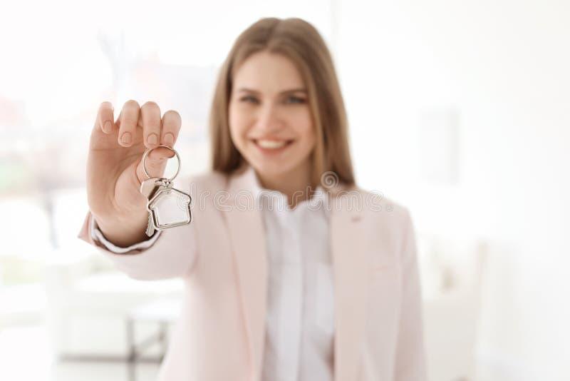 Piękny agent nieruchomości z kluczem indoors fotografia royalty free