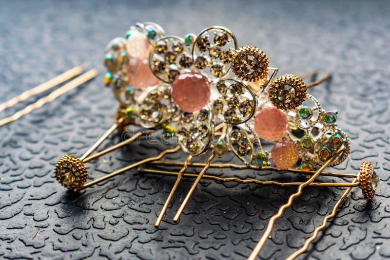 Piękny automatyczny barrette z błyszczącymi kamieniami i różowymi koralikami na zmroku textured tło Złociści hairpins z białymi r obrazy stock