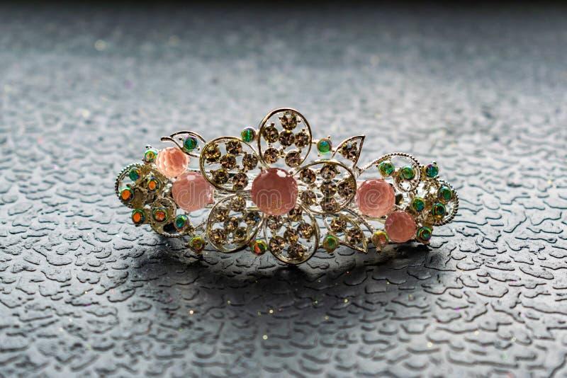 Piękny automatyczny barrette z błyszczącymi kamieniami i różowymi koralikami na zmroku textured tło Złociści hairpins z białymi r zdjęcie stock