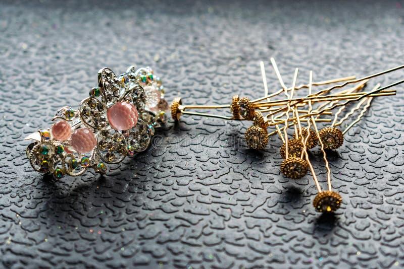 Piękny automatyczny barrette z błyszczącymi kamieniami i różowymi koralikami na zmroku textured tło Złociści hairpins z białymi r zdjęcia stock