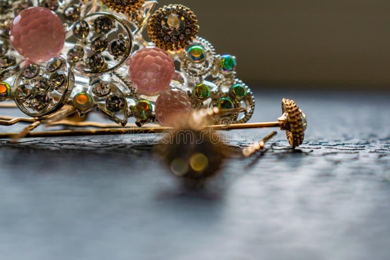Piękny automatyczny barrette z błyszczącymi kamieniami i różowymi koralikami na zmroku textured tło Złociści hairpins z białymi r fotografia stock