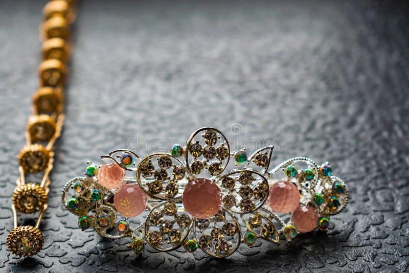 Piękny automatyczny barrette z błyszczącymi kamieniami i różowymi koralikami na zmroku textured tło Złociści hairpins z białymi r obrazy royalty free